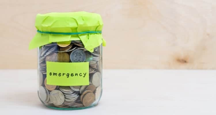 a jar full of money with the word emergency written on the outside