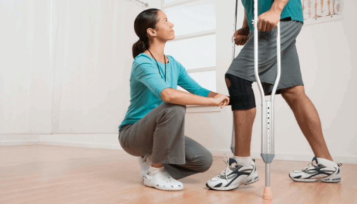 physical therapist looking at patients knee